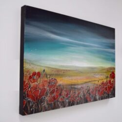 A hazy summer sunrise landscape consisting of golden fields and bright red poppies in the foreground.